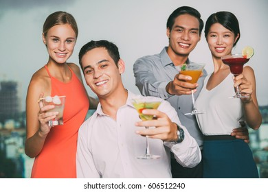Two Smiling Young Couples Raising Glasses in Bar