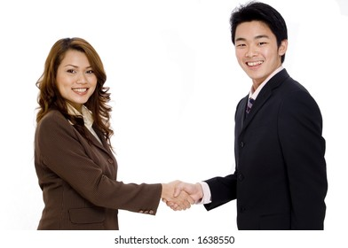 Two smiling young executives shaking hands