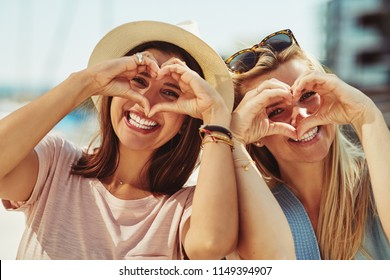Two smiling young friends making heart shapes with their hands while having a fun day out together in summer