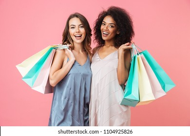 Two smiling young girls dressed in summer clothes holding shopping bags isolated over pink background