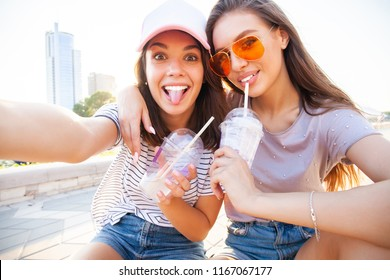 Two smiling young girls having fun while sitting on a skateboard and taking a selfie at the park