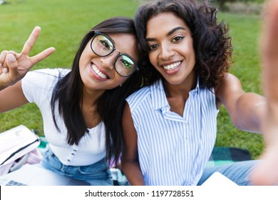 Two smiling young girls students sitting on a grass at the campus, studying with laptop computer, taking a selfie