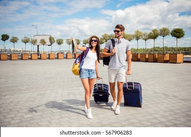Two smiling young  lovers with valise walking from airport in town.