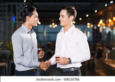 Two Smiling Young Men Shaking Hands at Party
