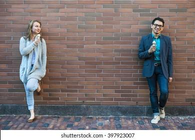 Zwei lächelnde junge Leute, die Eis halten, die in der Nähe einer Ziegelwand mit Kopienraum auseinander stehen
