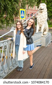 two smiling young traveller lass stand on Lion's Bridge in Saint-Petersburg, Russia