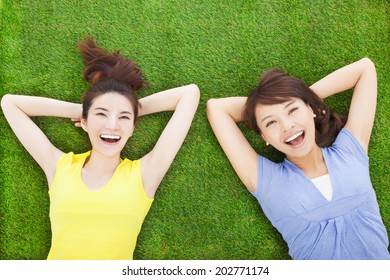 two smiling  young woman lying  on meadow