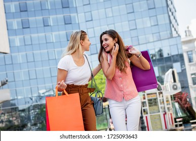 Two smiling young woman walking down the street after sopping, carrying bags in their hands.
