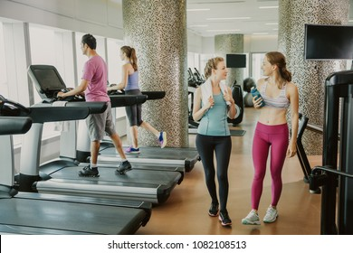 Two smiling young women chatting, relaxing, wearing sportswear and walking in gym. One woman is holding bottle of water. Another woman and man are training on treadmills. Full length view.