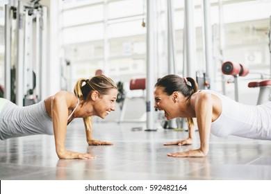 Two smiling young women exercising in a gym