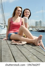 Two smiling young women sitting on the berth at summer day