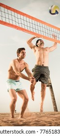 Two smilling male are playing in volleyball in time resting near ocean.