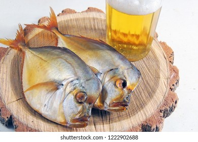 Two smoked Selene setapinnis, also known as Atlantic moonfish or Vomer setapinnis, on a white dish and the glass of lager beer on the old rustic table with fishing net