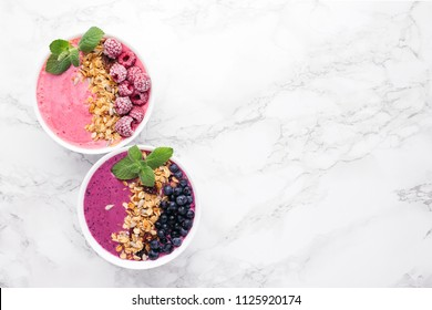 Two smoothie bowls with granola, blueberries, raspberries and mint on marble background. Healthy breakfast, top view.
