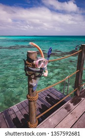 Two snorkel masks drying out on a wooden pillar next to a shower on the deck of an over water bungalow which has direct access to the tropical water of the south pacific.