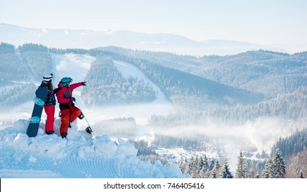 Two snowboarders enjoying beautiful natural landscape, resting on top of the mountain on a sunny winter day at ski resort. Man pointing to the background copyspace snowboarding lifestyle recreation