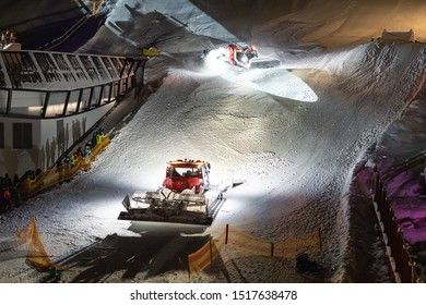Two snowcat ratrack machines making night show performance on snow pister hill at alpine skiing resort Ischgl in Austria