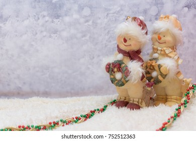 Two snowman ornaments on a winter background. Pathway is decorated with Christmas beads.