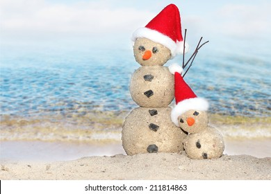 Two Snowmen at sea beach in santa hats
