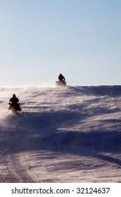 Two snowmobiles driving up a hill in a snow storm