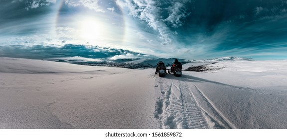 Two snowmobiles with one driver stand in front of dramatic scenic Sunset view at cold snowy Norwegian Mountains, Sun halo shines on cold skies, View at Norway from Swedish side of border, Lappland