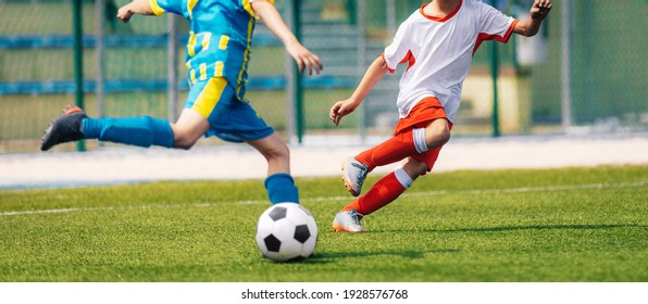 Two Soccer Boys Kicking Ball in Opposite Teams. Football Duel; Kicking Ball Moment. Young Football Players Running in Duel and Playing Soccer Tournament Match. Sports Competition for Youth Athletes