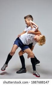 two soccer players interfere with each other, compete. studio portrait of young football players