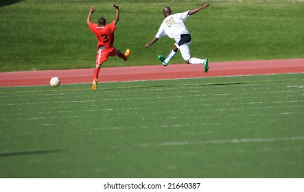 Two soccer players jumping wacky after the ball