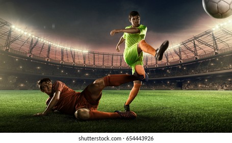 two soccer players on a field fighting for a soccer ball