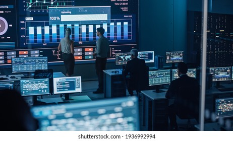 Two Software Engineers Talking Next to a Big Screen in a Modern Monitoring Office with Live Analysis Feed with Charts. Monitoring Room Big Data Scientists and Managers Sit in Front of Computers.