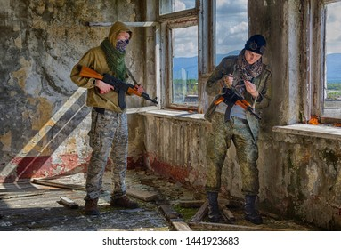Two soldiers of fortune or criminals in camo clothes and mascs with machine guns and knives inside of abandoned building. Ambush (one of them look in the window)