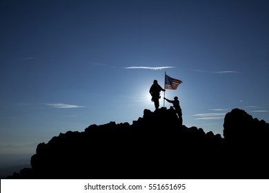 Two soldiers raise the American flag on top of the mountain