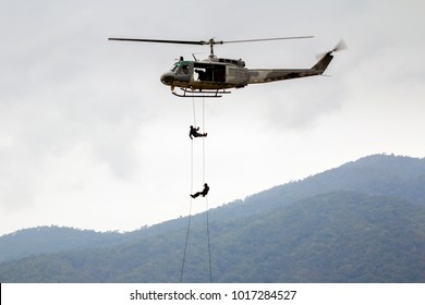 Two Soldiers are Rappelling from Helicopter for Demonstration Rescue Mission on Children Day Air Show at Chiang Mai International Airport with Mountain Background. Copy Space for Text.