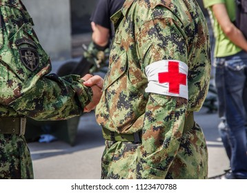 """Two soldiers are shaking hands, one on the sleeve has an inscription and the coat of arms """"Military police"""" is the second red cross symbol."""