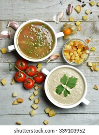 Two soup bowls composition vegetarian mushroom and fish cream soup in bowl with garlic parsley dill and croutons on rustic wood background
