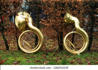 Two Sousaphones standing at a hedge. The Sousaphone is a large, ring-shaped instrument that is often used in the marching band guggen music.