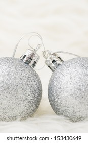 Two sparkling silver colored christmas baubles