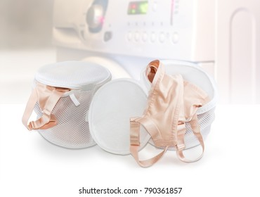 Two special mesh bags with zipper for washing bras and other small clothing and accessories and bras in them on a blurred background of washing machine