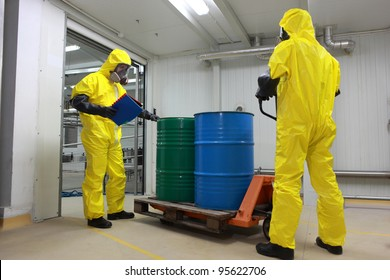 Two specialists in protective uniforms,masks,gloves and boots  transport barrels of chemicals on forklift in factory