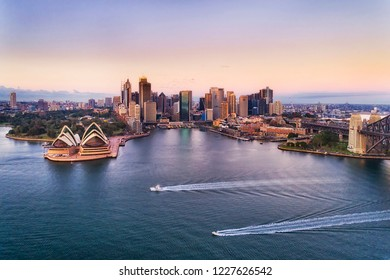 Two speed boats on calm waters of Sydney harbour in view of Circular quay and city CBD high-rise towers and Australian landmarks at sunrise with pink sky.