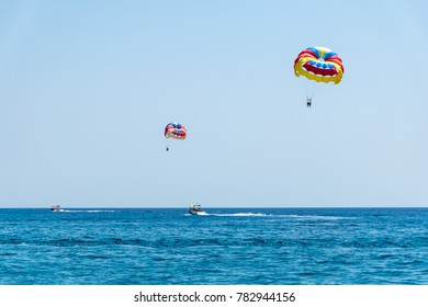 Two speed boats with people flying on parasailing parachute (RHODES, GREECE)