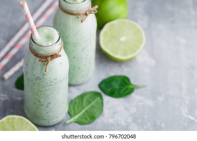 Two spinach smoothies with lime in the glass bottles with straws