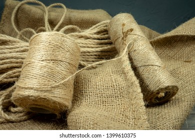 Two spools of burlap threads or jute twine and coil of linen rope on sackcloth fabric in close-up on grey background