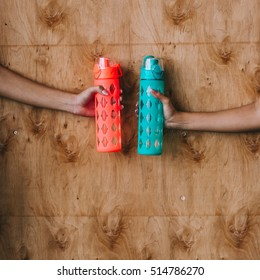 two sports bottle for drinking in women's hands on the wooden background