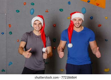 Two sports guys in santa hats happily posing and showing thumb up. Against the wall for climbing.