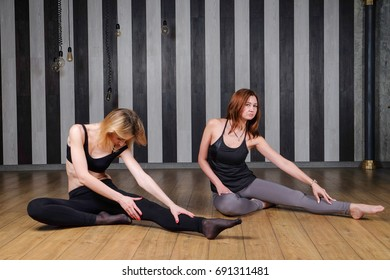 Two sports woman. Fitness instructor. Lesson with a trainer. Two women doing stretching back to help complete the exercise.