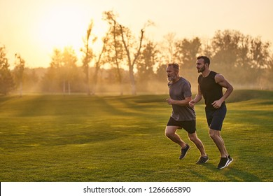 The two sportsmen running in the picturesque park on the sunset background