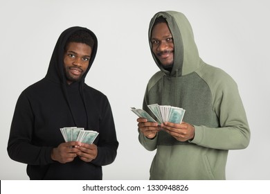 two sporty african men in tracksuits on a white background with dollars in their hands