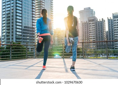 Two sporty asian women stretching for warming up before running. Female urban fitness workout, exercising outside, healthy life concept.