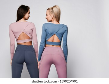 Two sporty blonde and brunette girls in athletic body cloth sport wear cloth stand together after workout on gray background